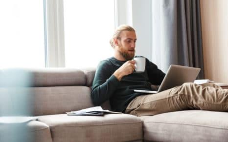 Mann som sitter i sofa med kaffekopp og laptop på fanget.