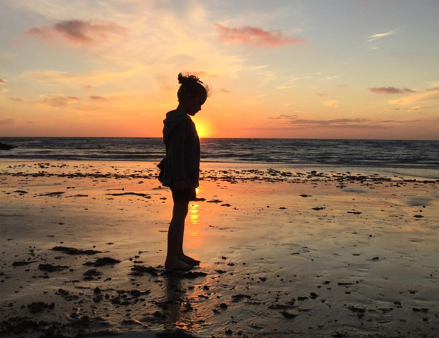 Jente i solnedgang på stranden