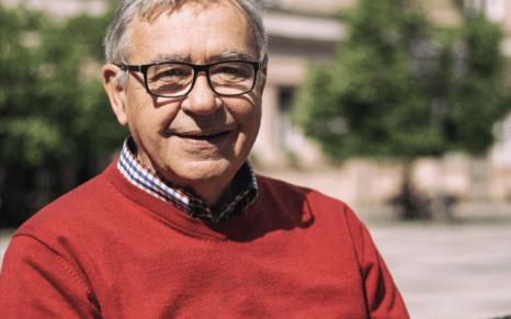 Portrettbilde av eldre mann med rød genser.