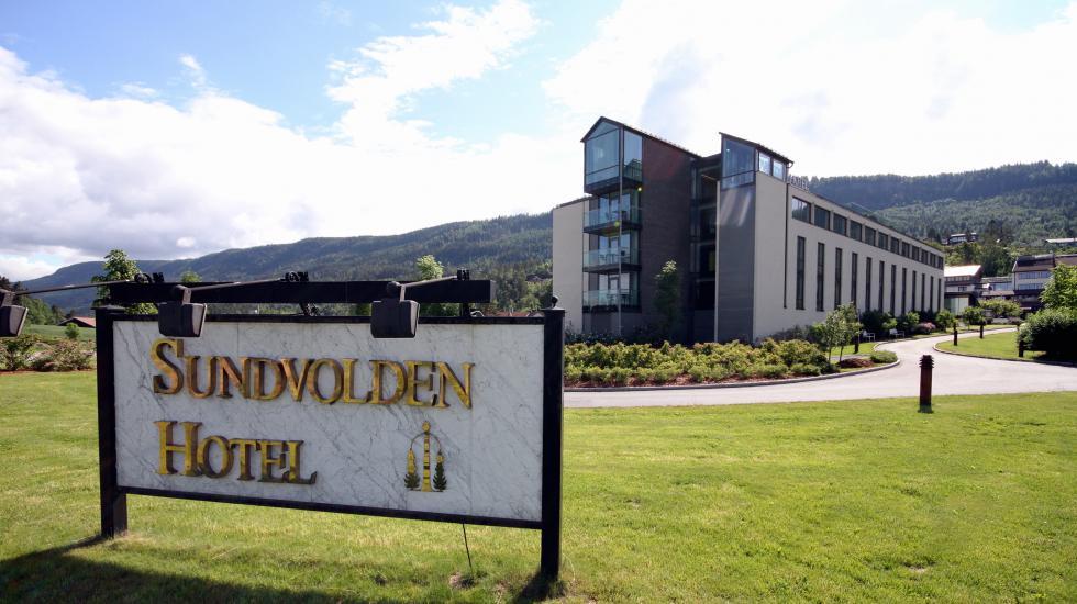 Skilt til Sunvolden hotell med hotellet i bakgrunnen.